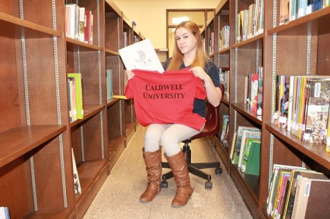 Erin Fallon showing off her acceptance with Caldwell University T-shirt and Kean University packet.