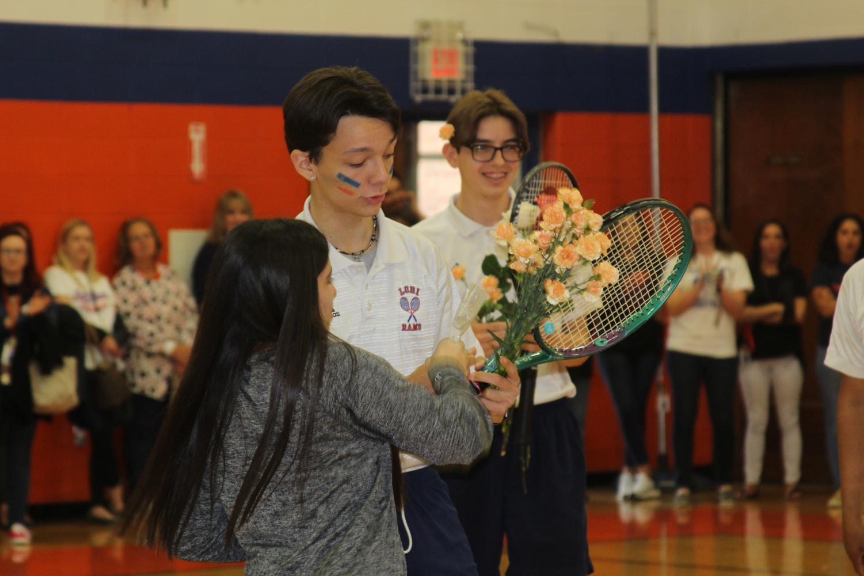 Secretary+Michelle+Guerra+handing+a+candy+bag+to+Boys+Tennis+player